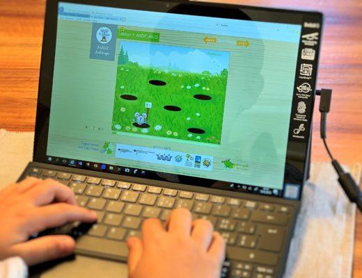 Kind lernt Tastatur Maschinen schreiben auf Tablet